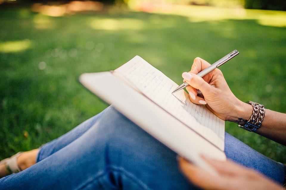 女性がノートに書きこんでいるところ