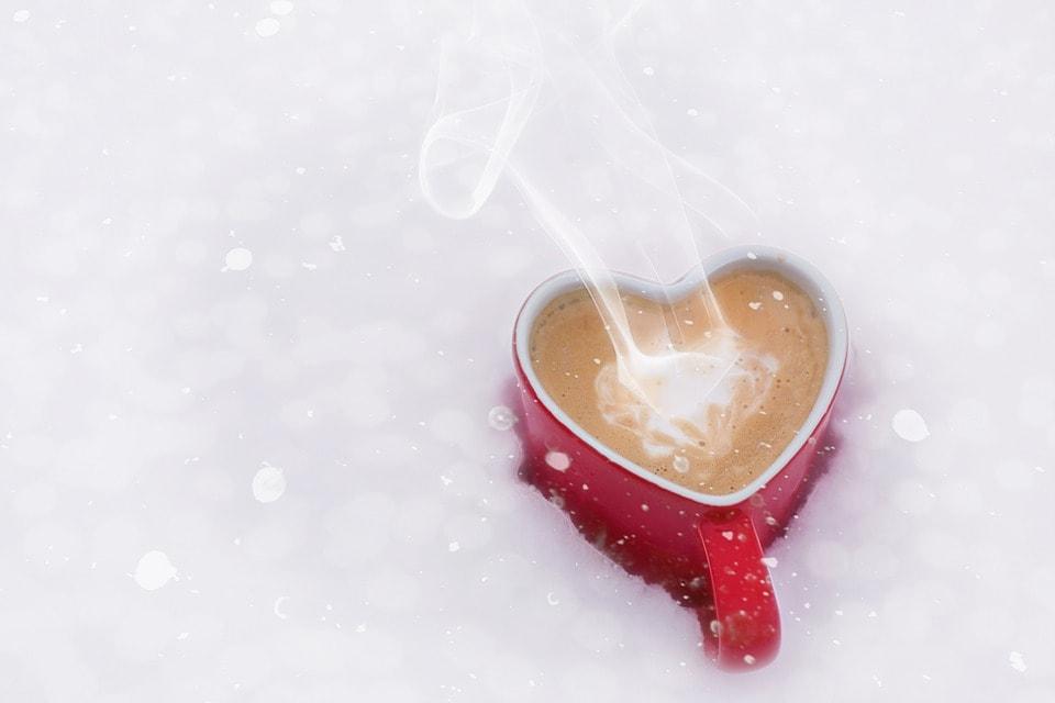 雪の中のハートのコーヒーカップ