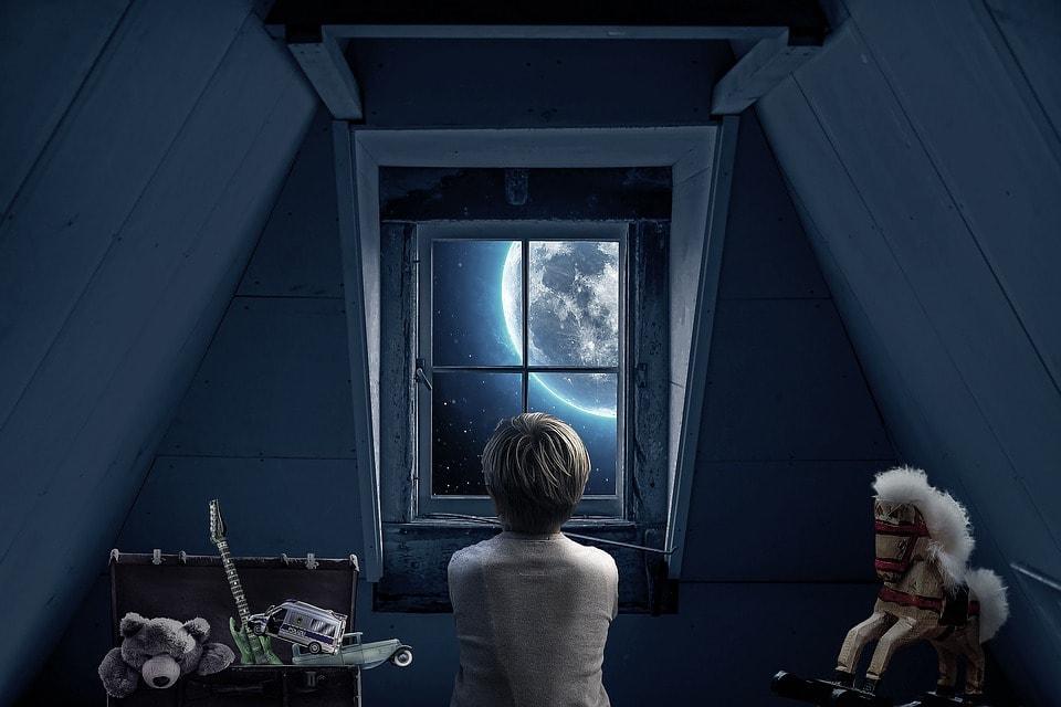 窓から月を見つめる少年