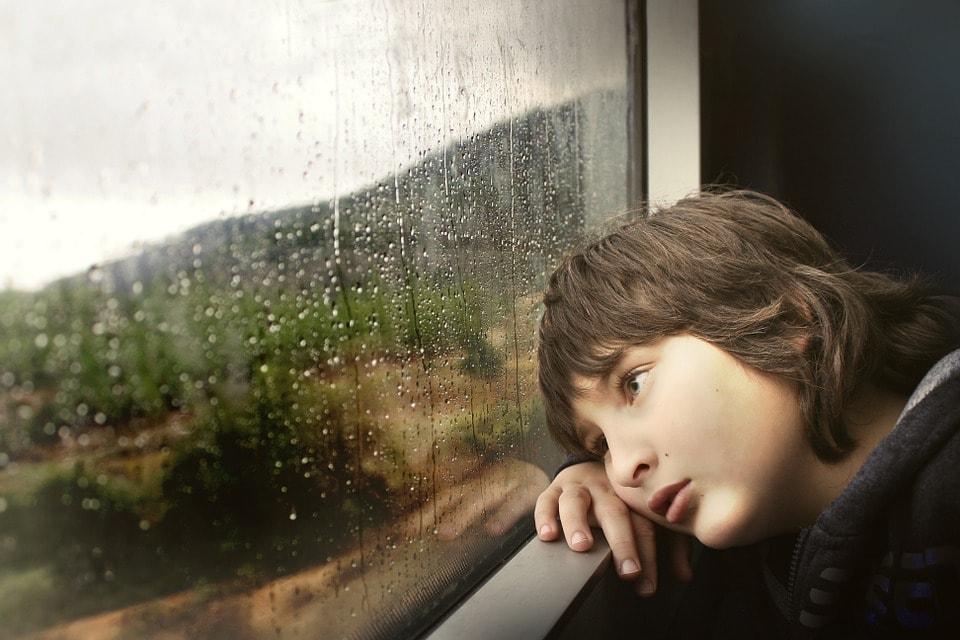 窓から雨の様子を見る少年
